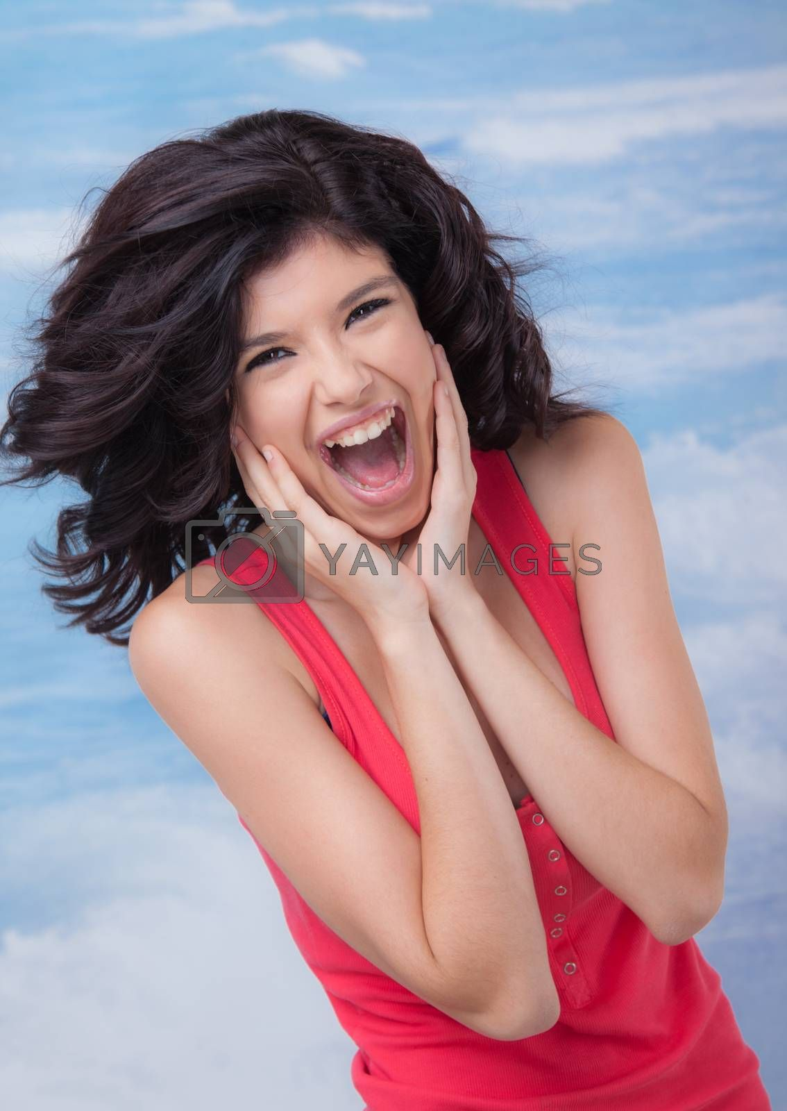Young beautiful female is screaming or laughing, holding face with hands.