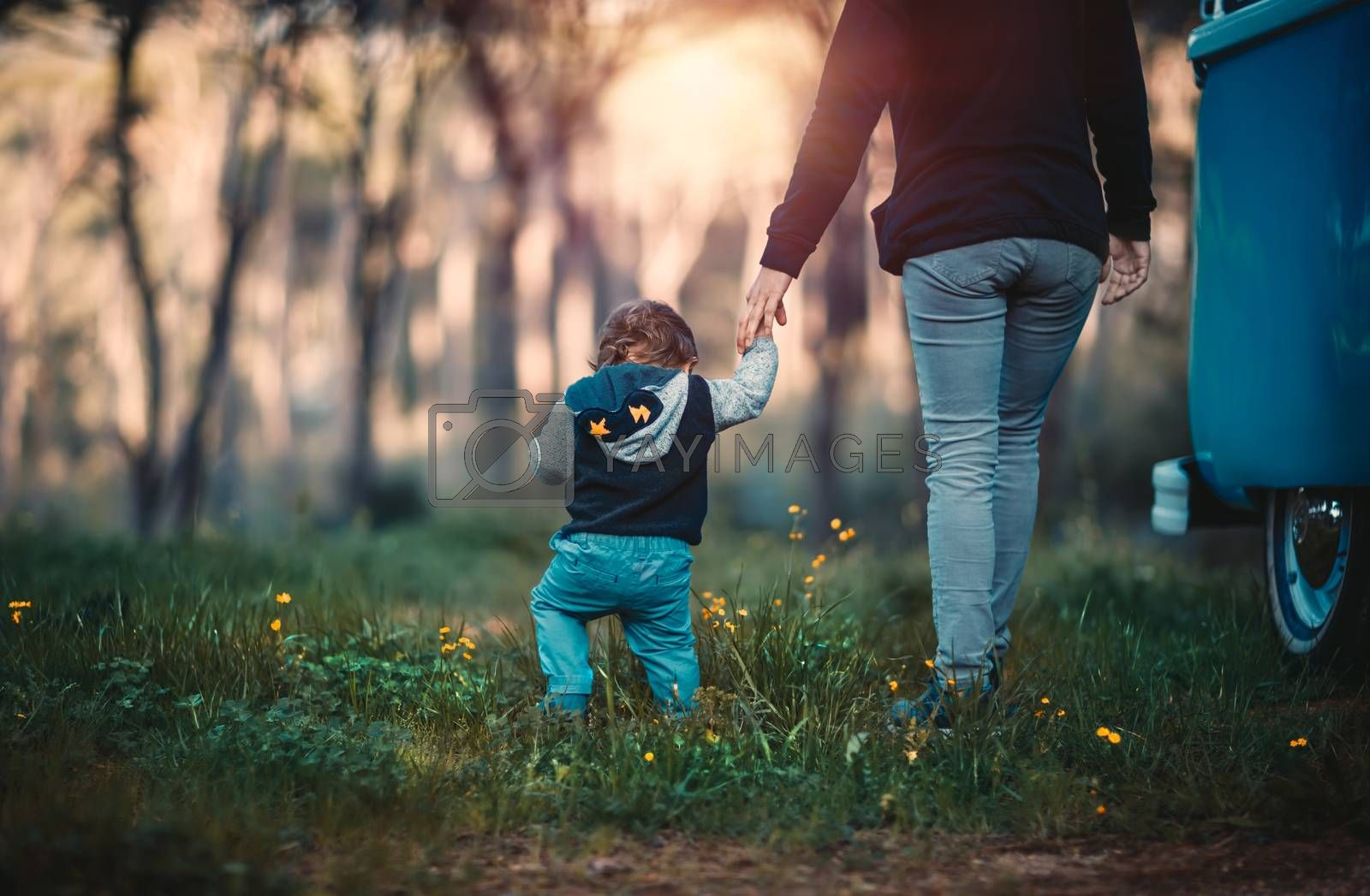 Mother with little son walking in the forest, weekend camping in the countryside, family enjoying spending time together, love and family support concept