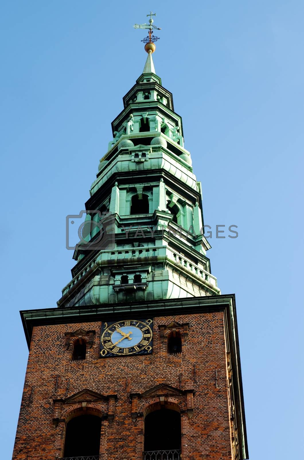 Spire of St. Nicholas Church against Blue Sky Outdoors Bottom View. Copenhagen, Denmark