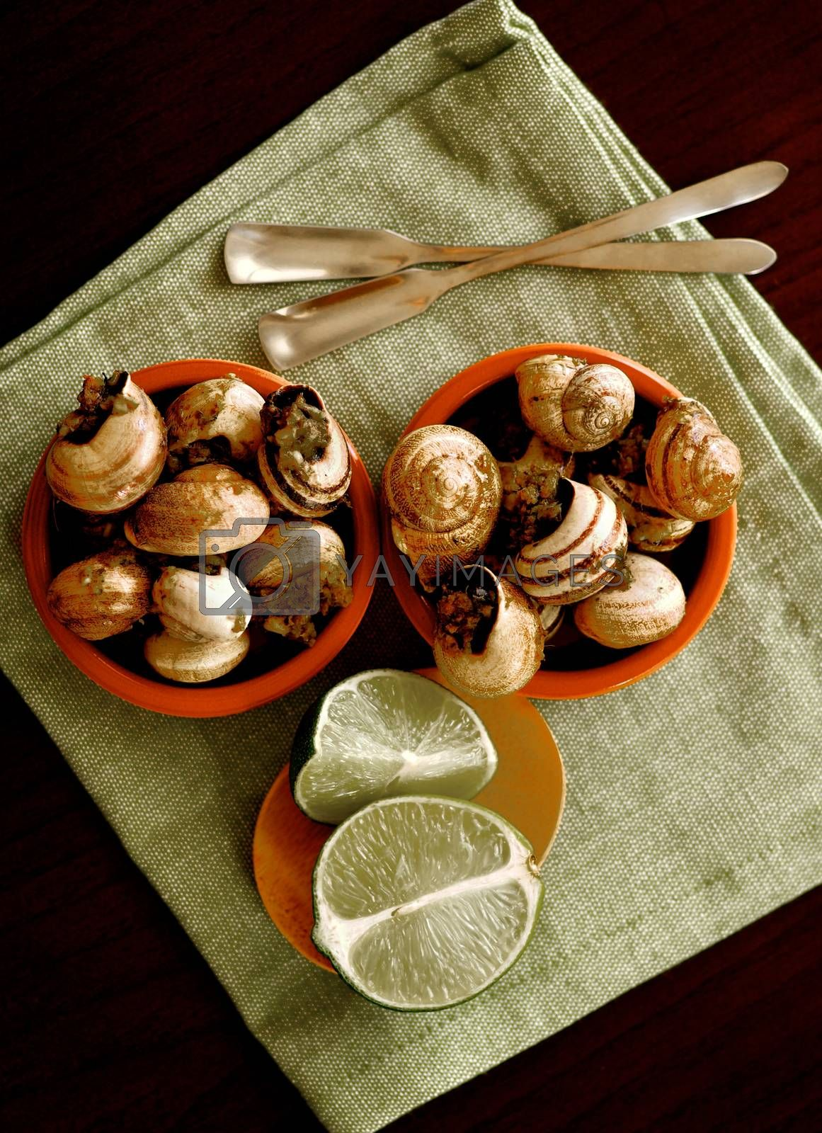 Two Bowls of Delicious Escargot with Garlic Butter, Silver Forks and Sliced Lime closeup on Green Napkin. Top View
