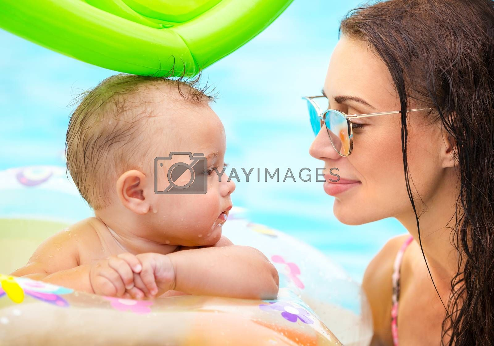 Closeup portrait of a beautiful mother with cute little baby in the pool, first lesson of swimming, enjoying summer holidays on the beach resort, happy family life