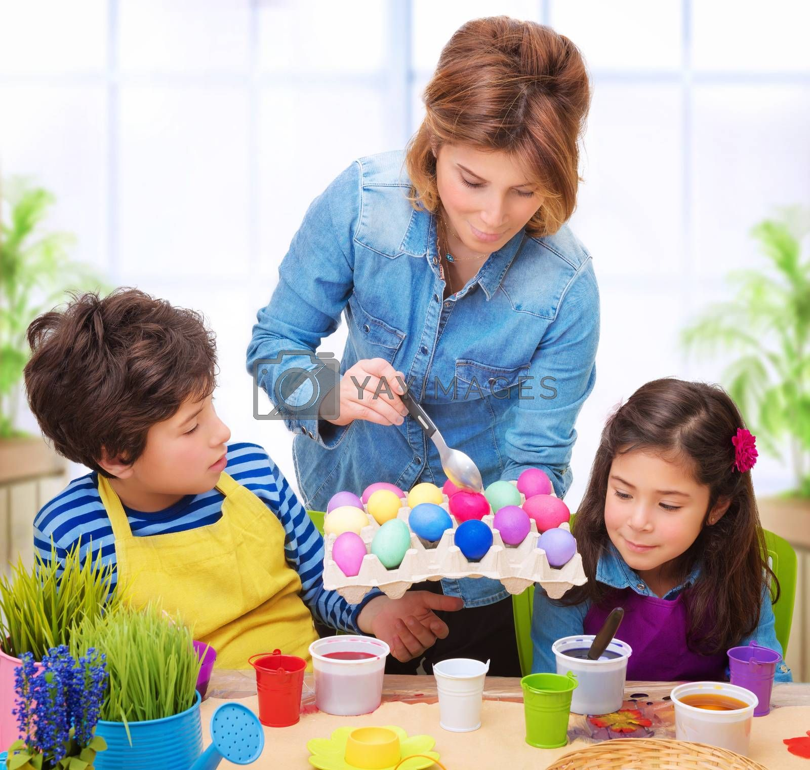 Happy family paint Easter eggs at home, mother showing her precious kids how to make traditional Easter decorative food