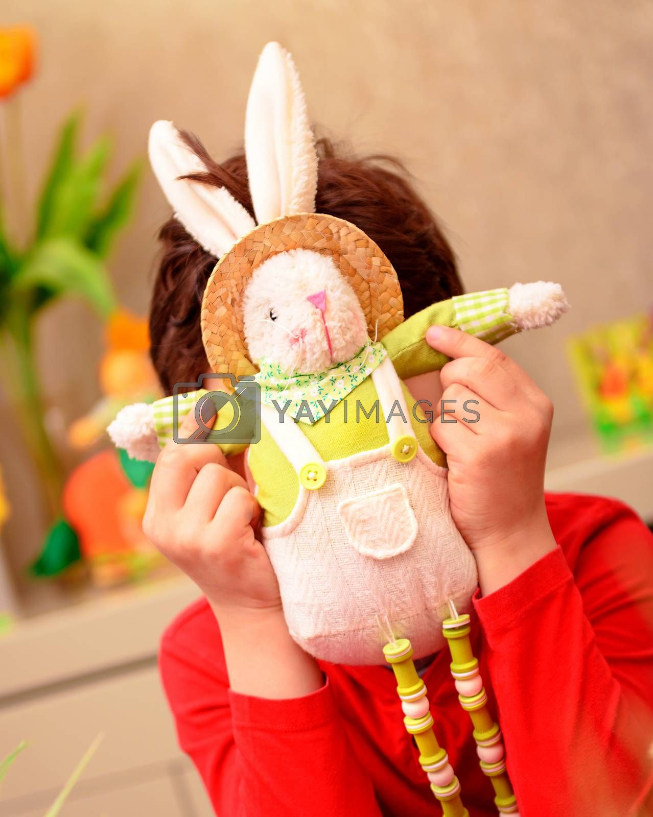Joyful boy playing with soft bunny toy at home, traditional Easter symbol, happy preparation to religious spring holiday