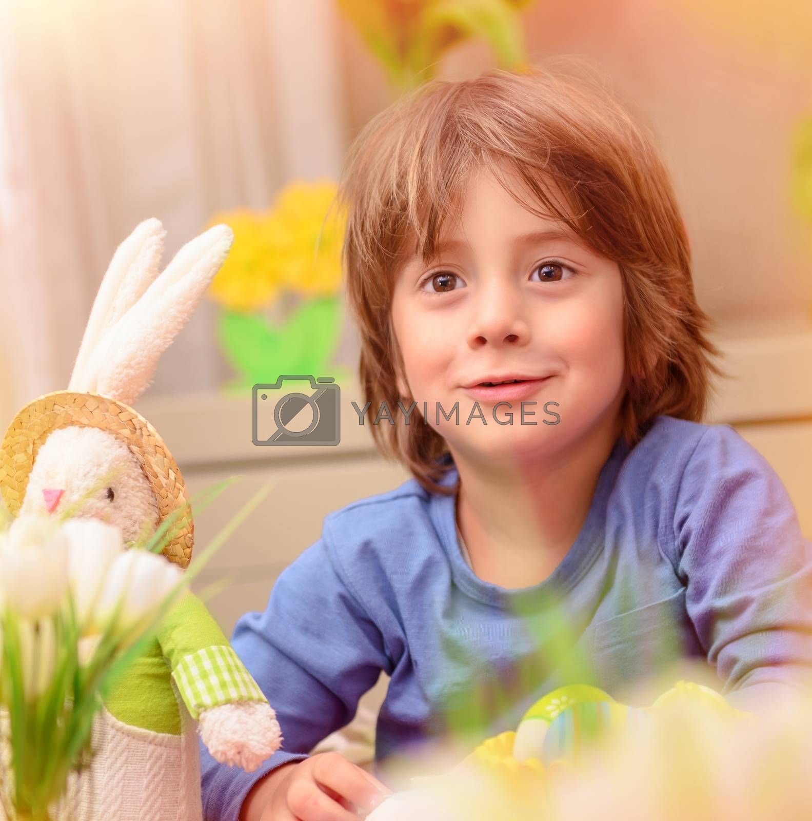 Portrait of cute little baby boy sitting in daycare and play with soft bunny toy and colorful eggs, with pleasure preparing to happy Easter holiday