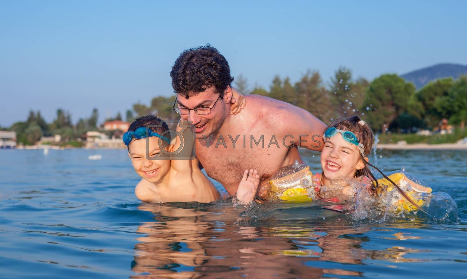 Young father having fun in sea waters during vacation in a hot summer day with his son and daughter.