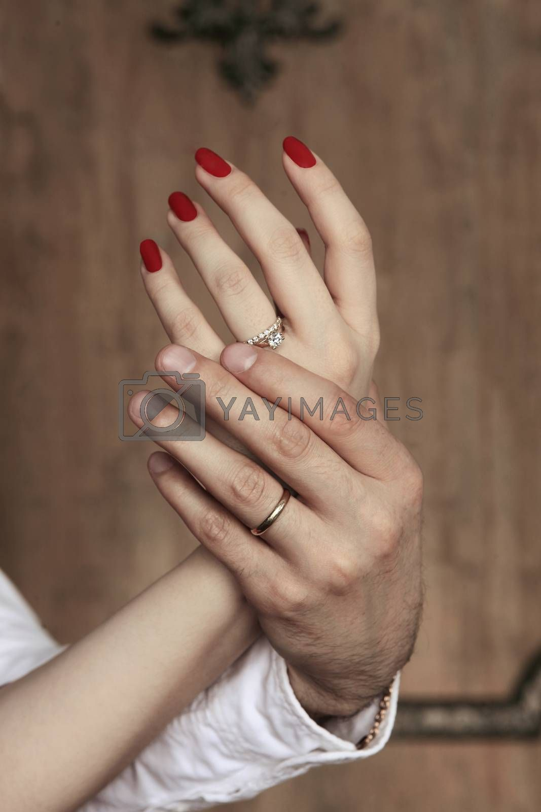 Female hands in man's hands on a wooden background