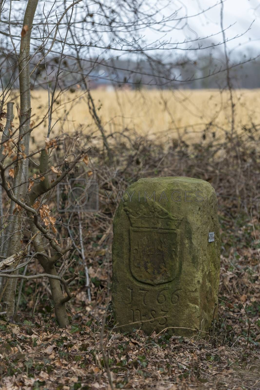 Historical boundary stone on the land border of Netherlands and Germany near the in Dutch called komiezenpaden paths in the past used by border guards and smugglers