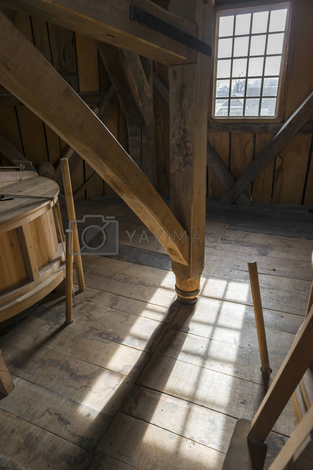 Interior of a historic wooden mill with a detail of an old wooden crusher in the area with beautiful light