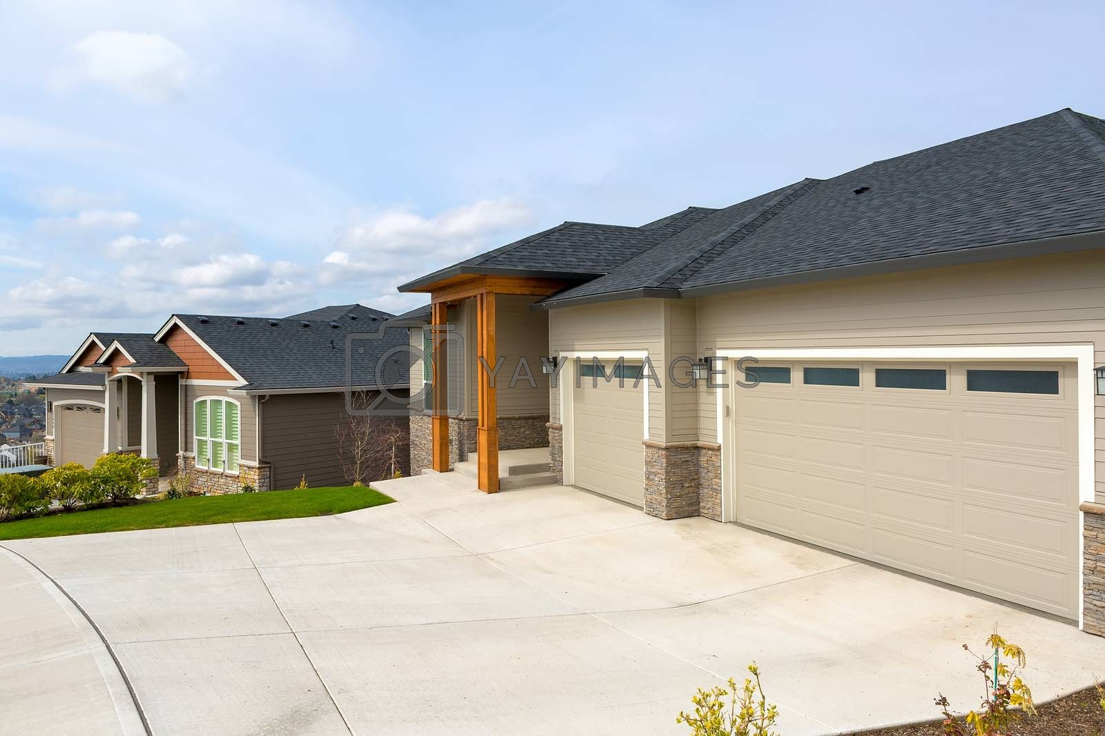 New custom built houses in Happy Valley Oregon suburban neighborhood with car garage driveway and manicured front lawn
