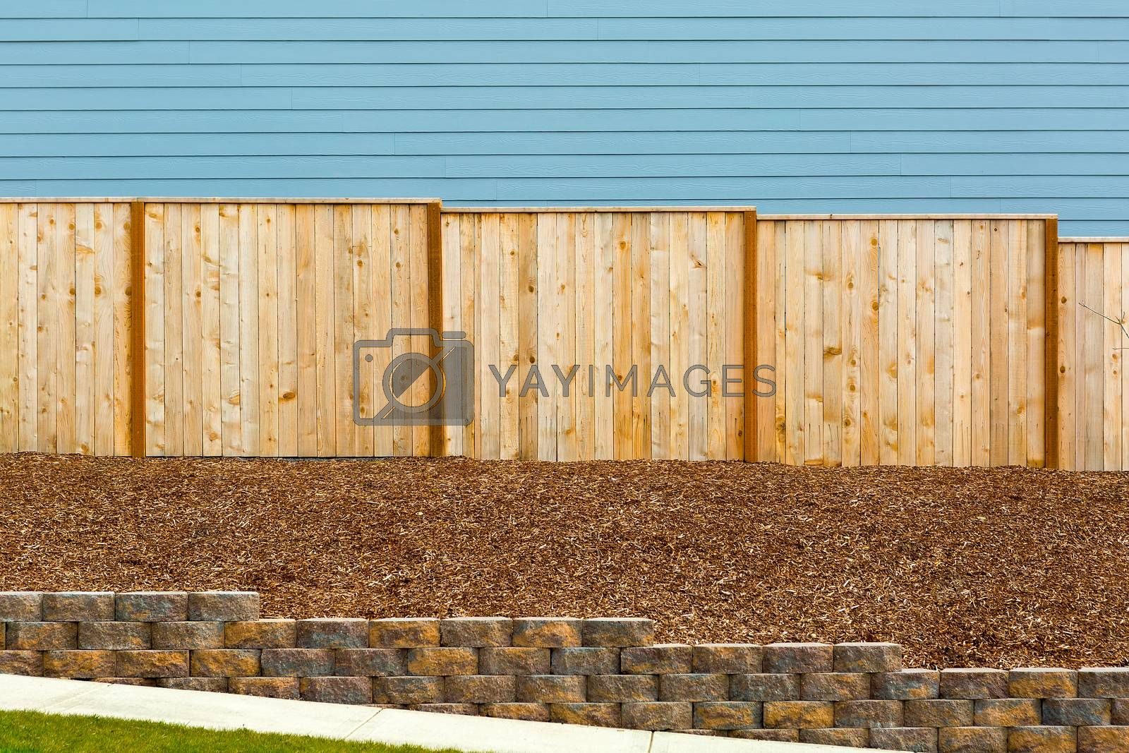 New Garden Wood Fence with house siding barkdust mulch concrete retaining wall along exterior sidewalk