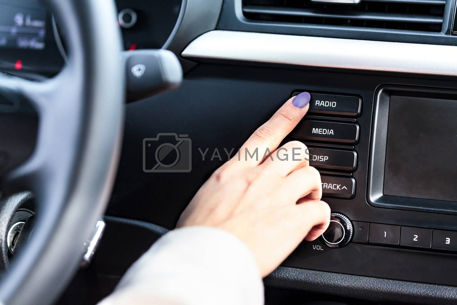Woman pressing radio button on car's control panel