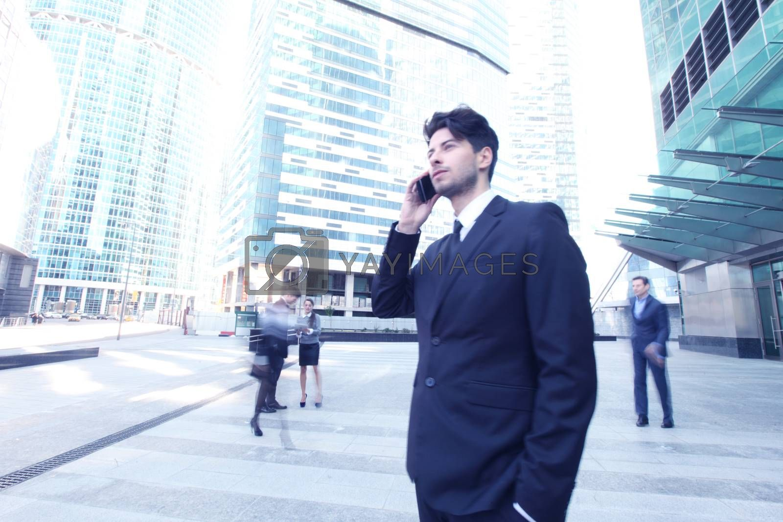 Handsome businessman talking on the cellphone outside office building