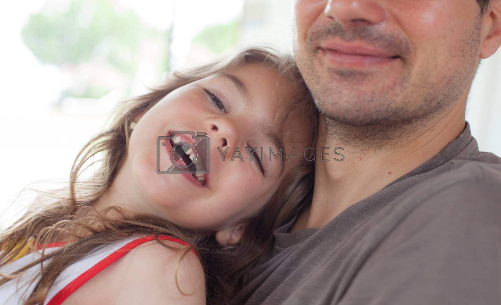 Close-up of a young smiling girl embraced by her father.