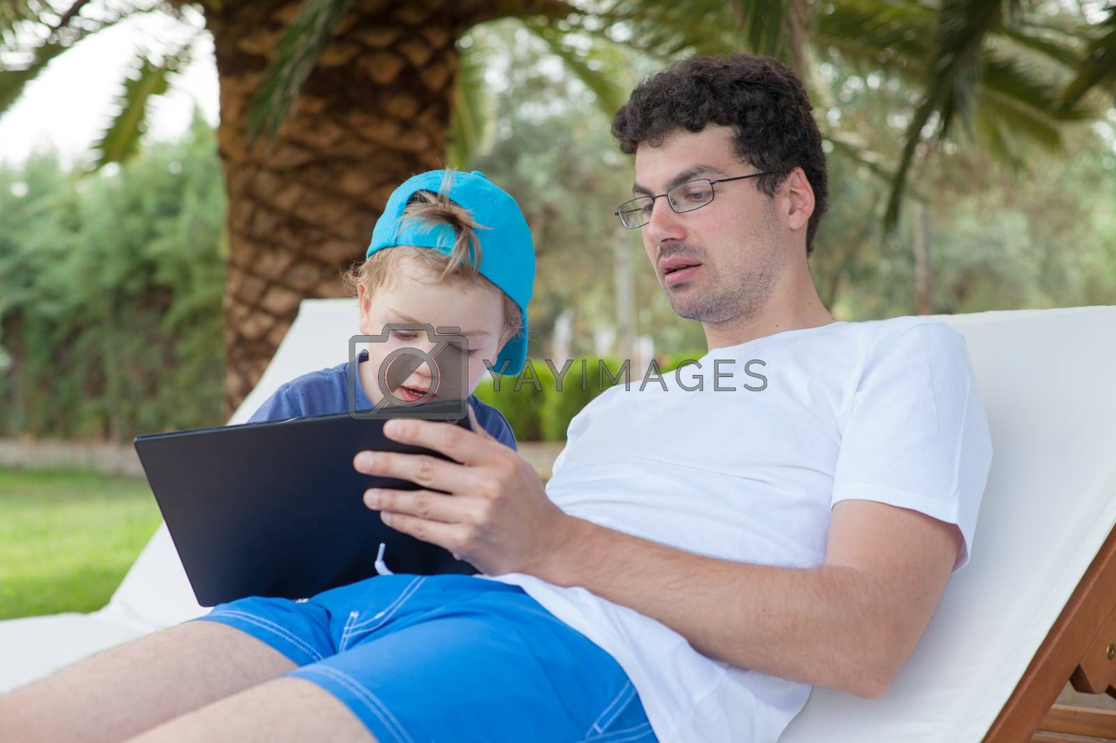 Young father showing something on tablet to his little boy outdoors.