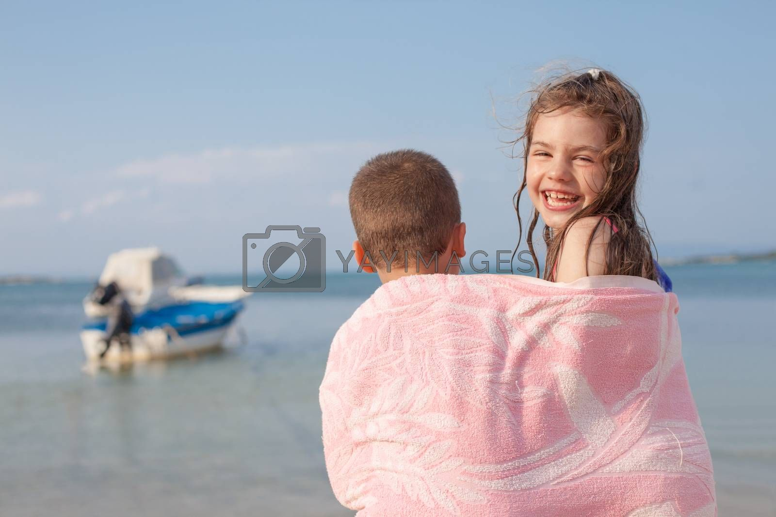 A girl looking to camera smiling and a boy with his back to the viewer, both sharing a towel