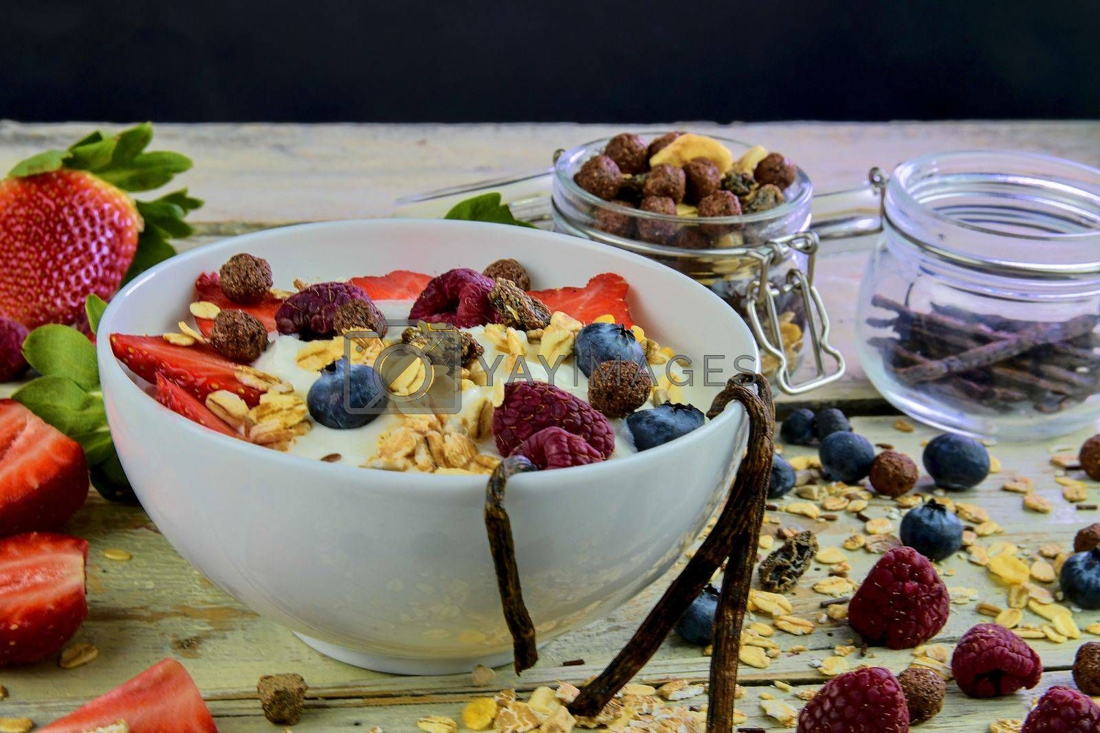 Healthy breakfast, cereal with yoghurt, strawberries, blueberries, raspberries and muesli on wooden rustic background.  Concept of: fitness, diet, wellness and breakfasts.