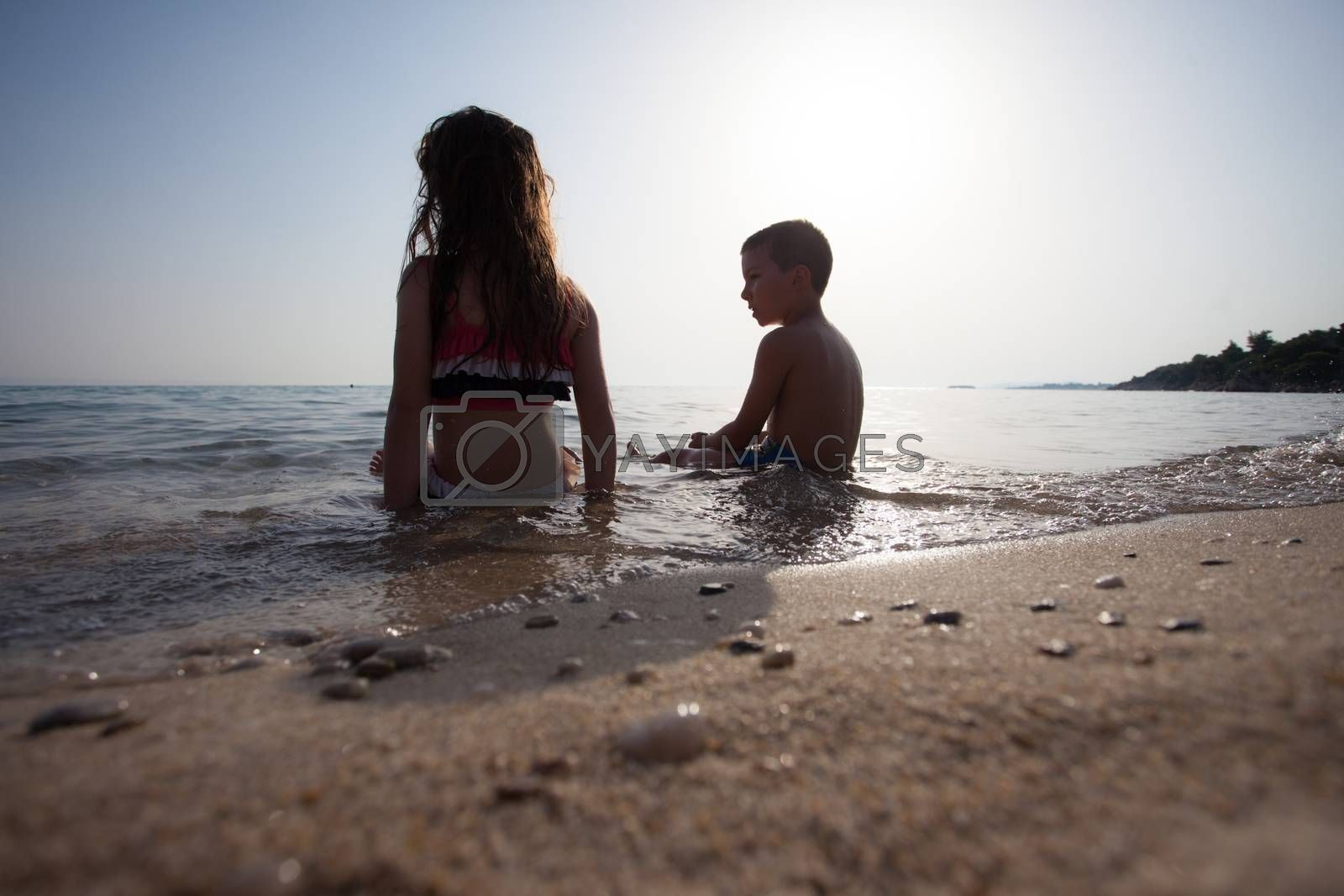 Couple of kids around six are sitting in the water of sea or ocean.