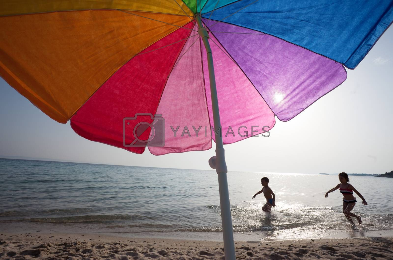 Couple of kids around 6 are playing in the water under the sun, colorful umbrella in foreground.