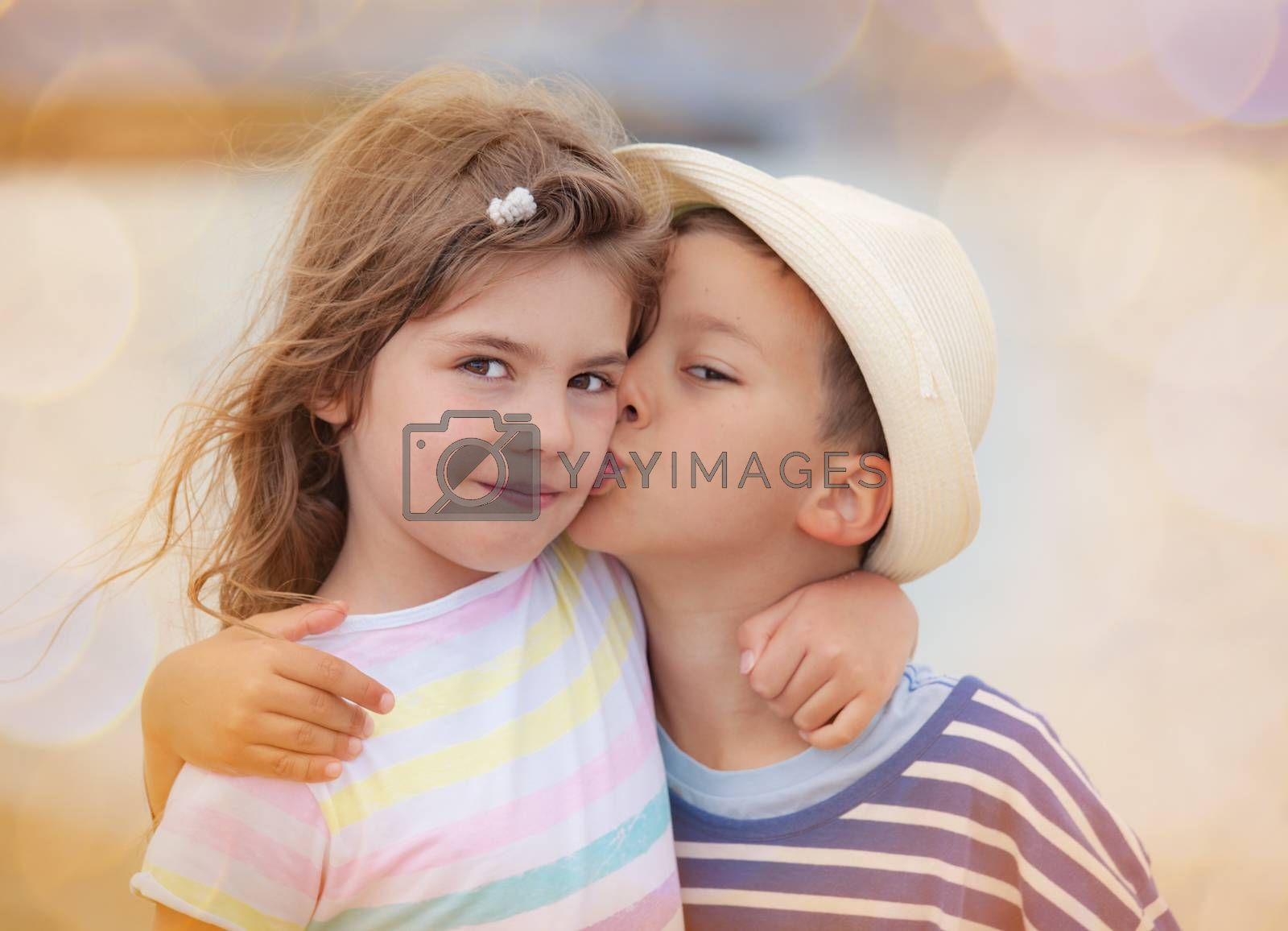 Young boy around six is kissing his sister on the chick
