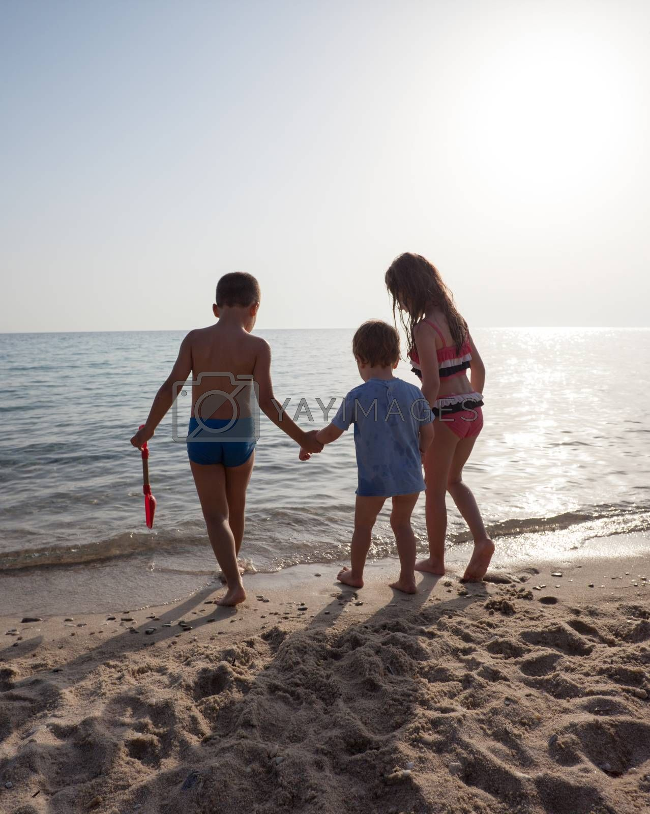 Three kids on the shore of a sea or ocean. Two are leading smaller one to the water.
