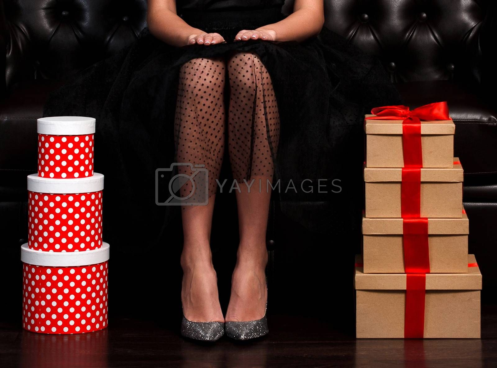 Pretty woman sittin on leather sofa between stacks of presents