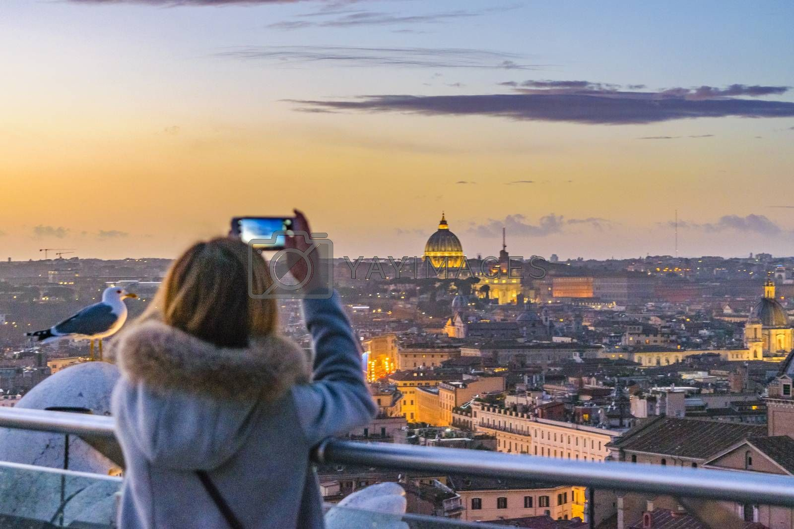 Woman taking a picture with smartphone of Rome cityscape from vitorio emanuelle monument viewpoint.
