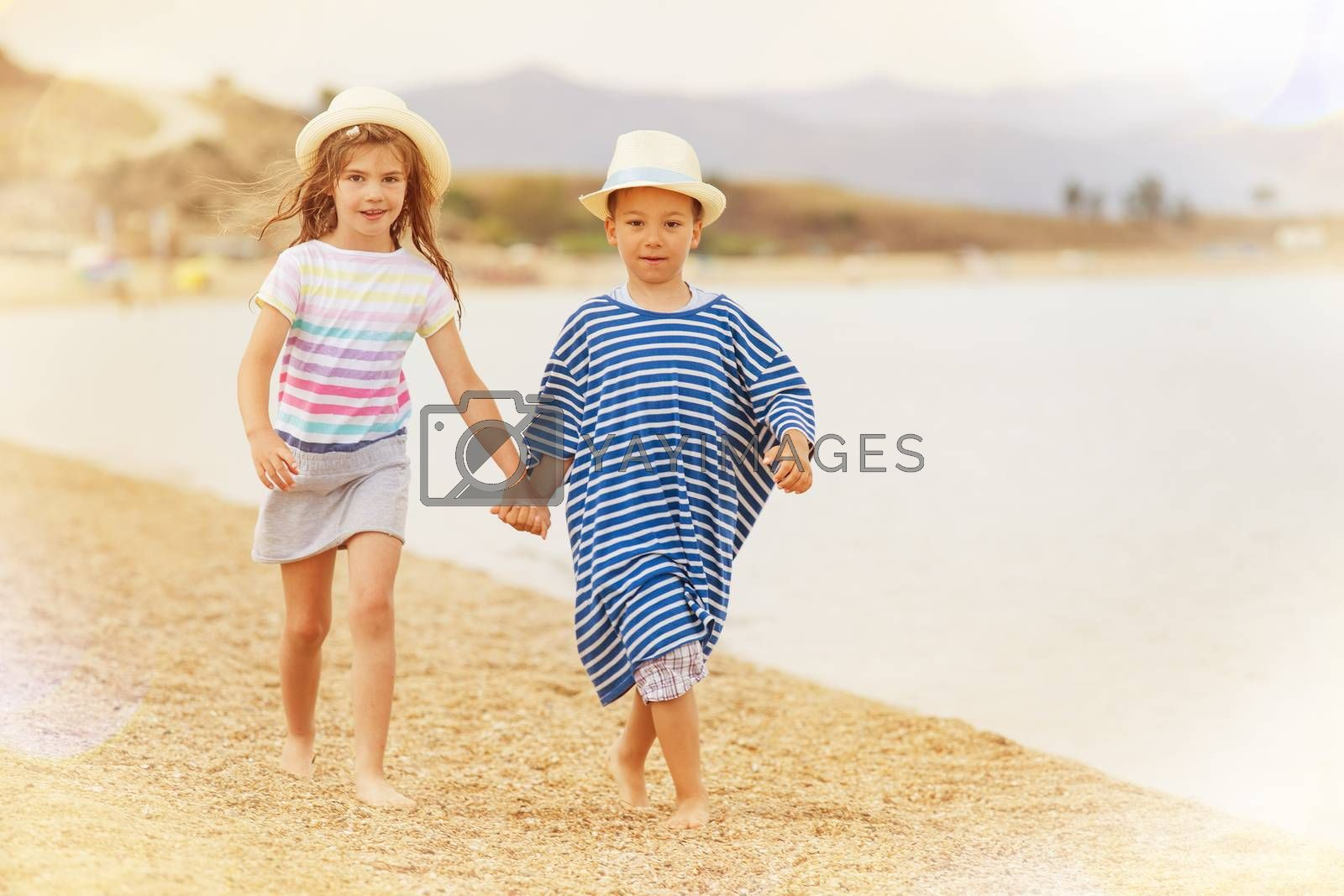 A boy and a girl around six holding hands while taking a walk on the beach smiling.