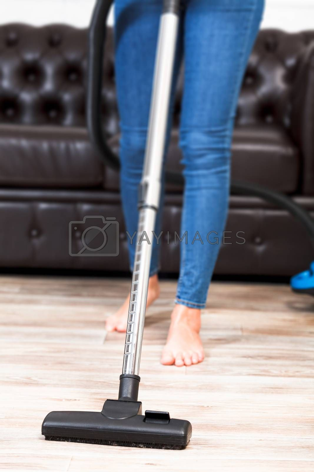 Housewife with a vacuum cleaner, closeup shot
