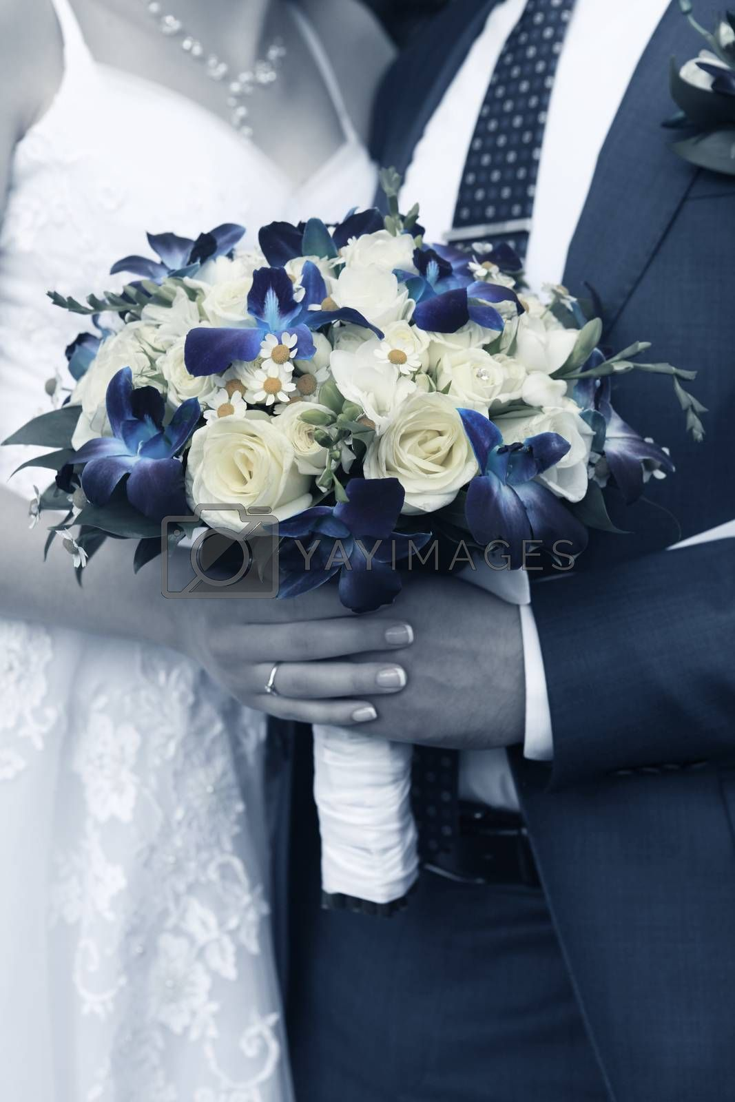 Hand of the groom and the bride with wedding bouquet
