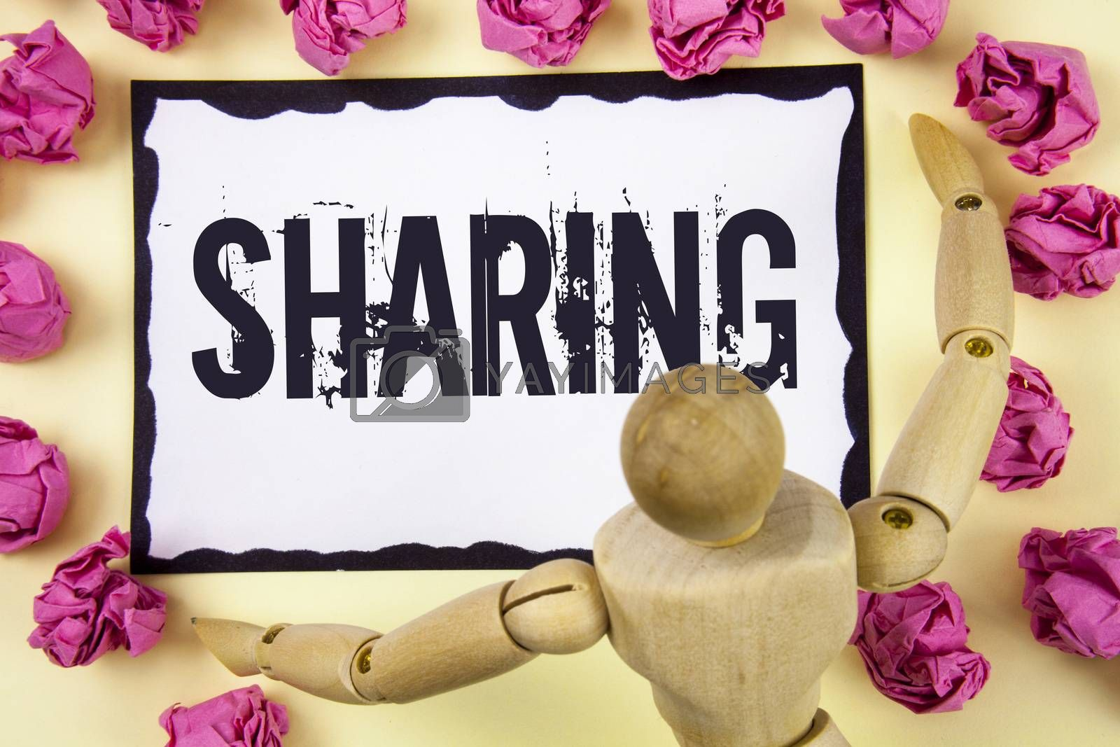 Handwriting text Sharing. Concept meaning To Share Give a portion of something to another Possess in common written Sticky Note Paper within Paper Balls plain background Wooden Robot Toy.