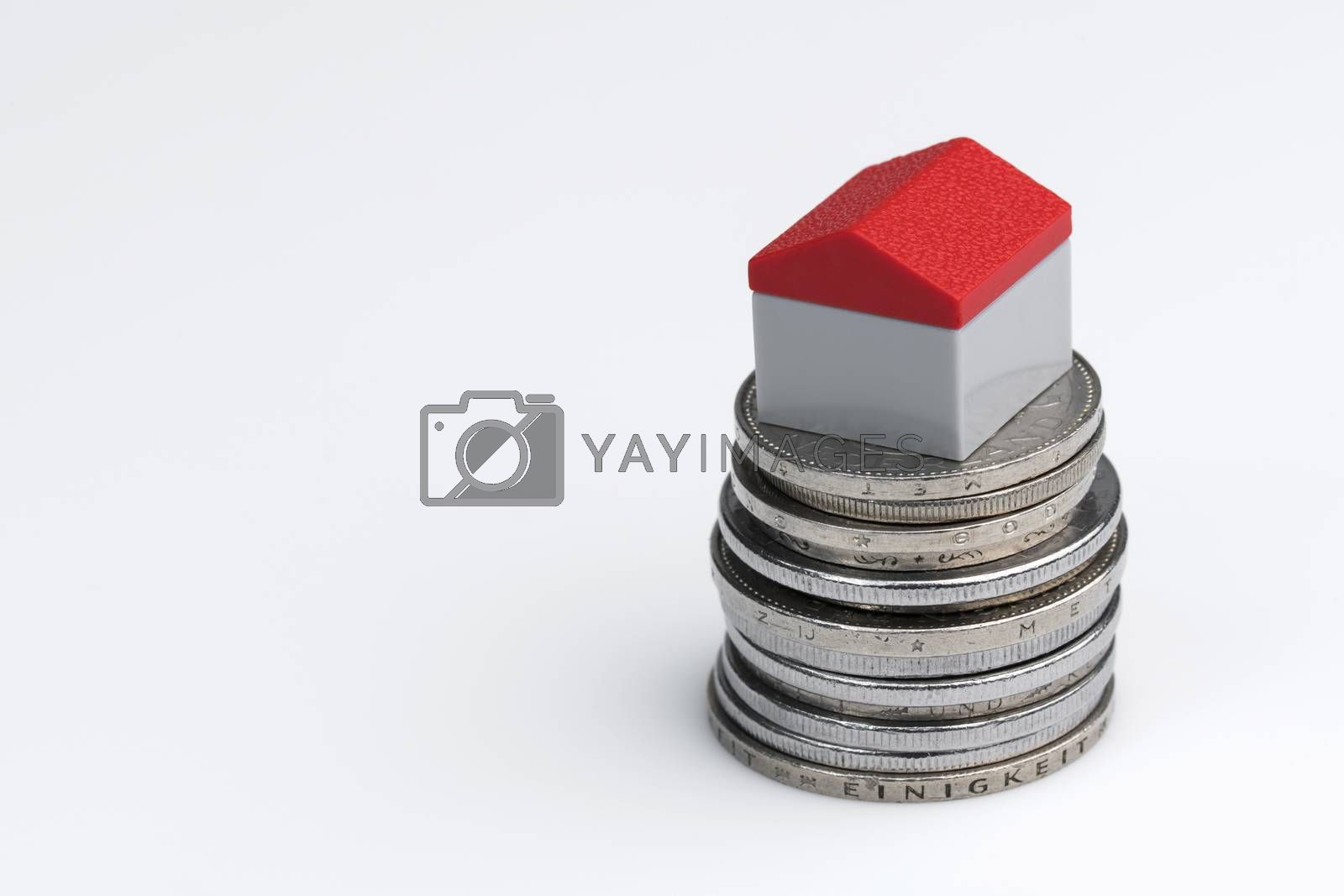 Conceptual visualization of property related financial act by means of coins with plastic miniature cottage for a white background