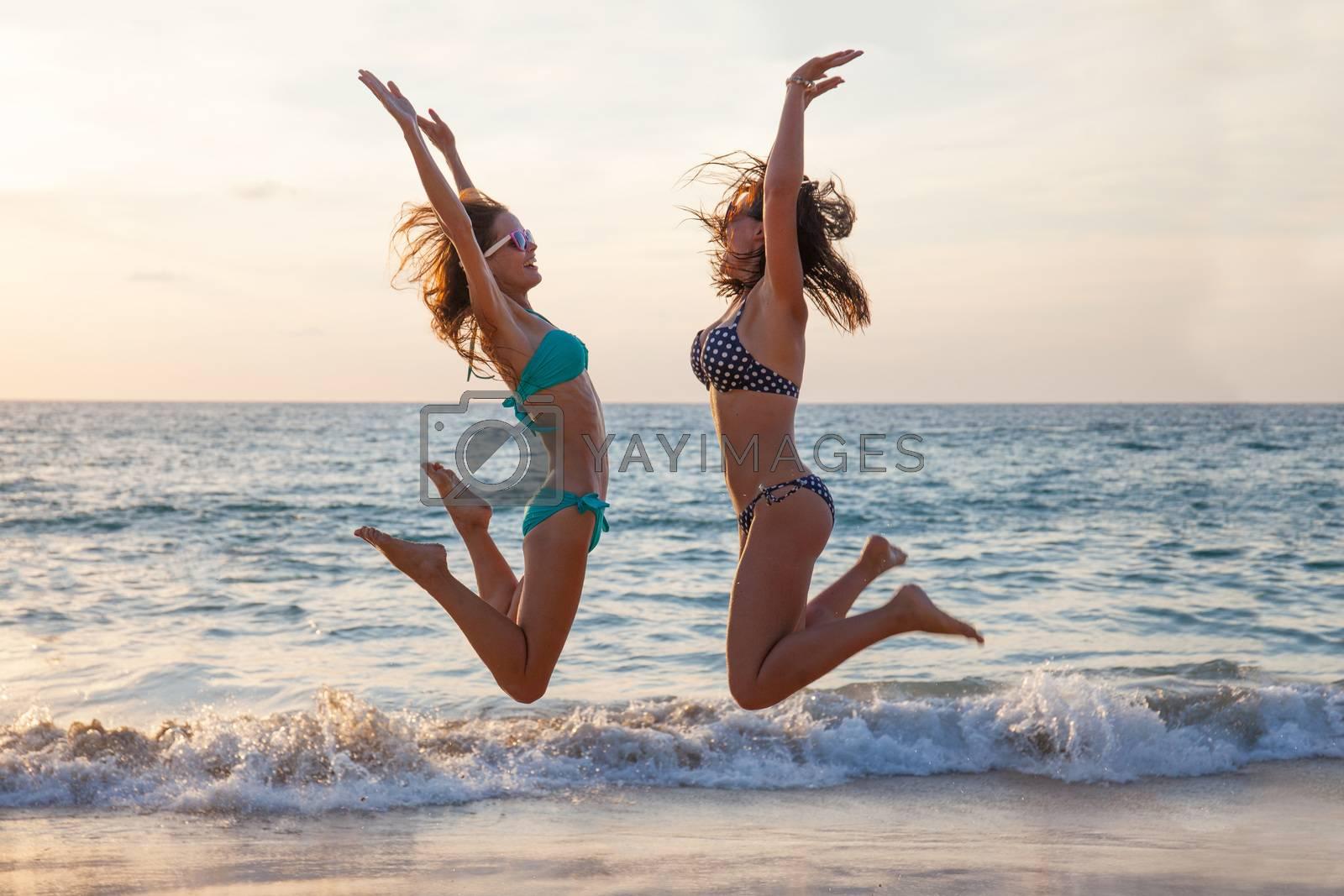 Happy female friends having fun on beach at sunset