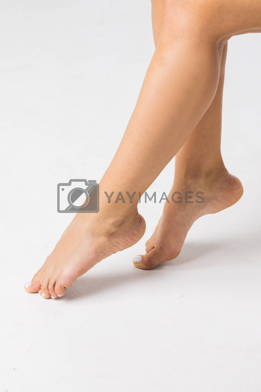 Young woman with perfect body is sitting with smooth silky legs after depilaton on a white background.Concept of depilation, smooth skin, skincare, cosmetics, wellness center,healthy lifestyle