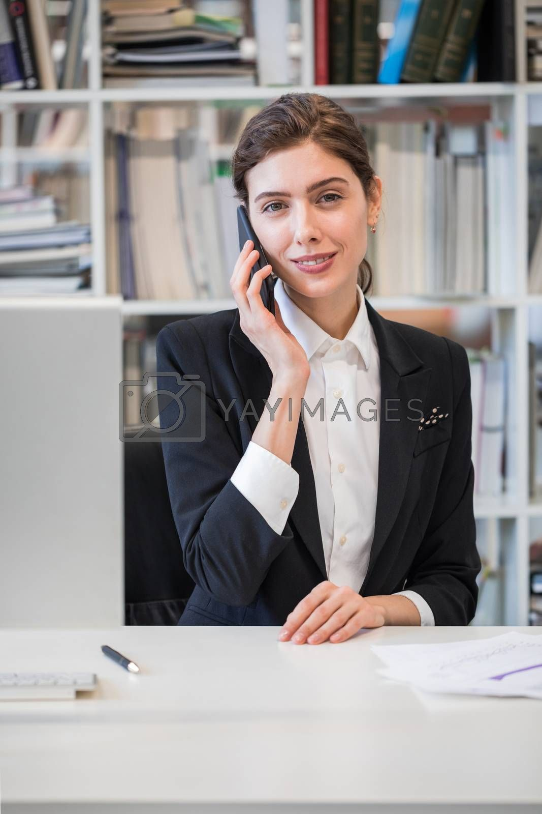 Beautiful mid age business woman talking on phone and looking at camera sitting at her working place in office