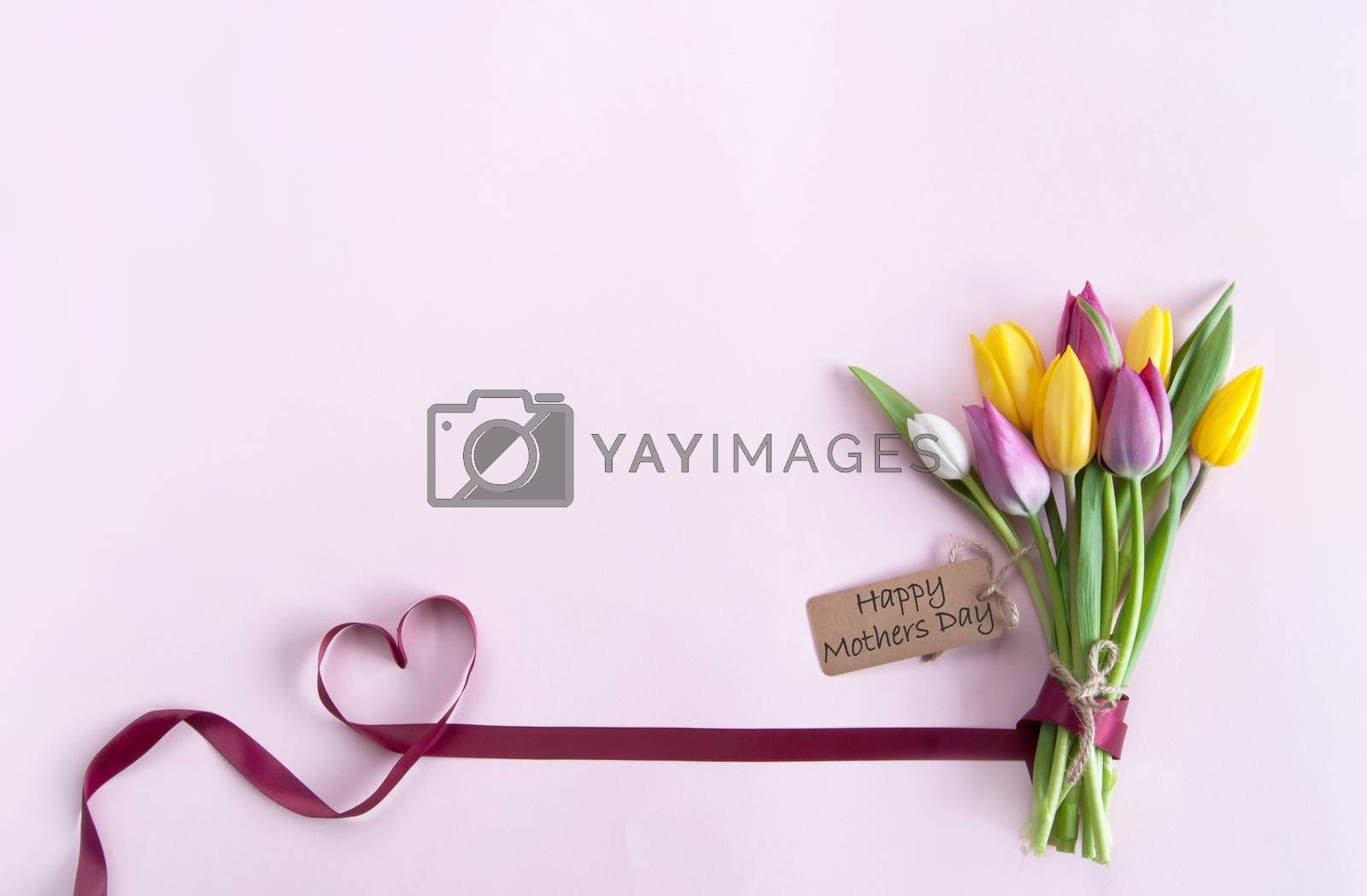 Heart shape ribbon attached to mothers day flowers with label