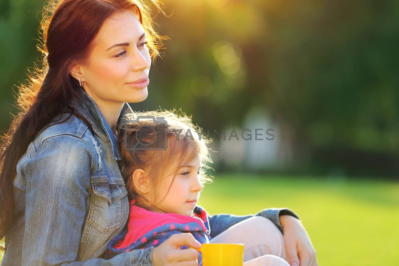 Portrait of mother with daughter relaxing outdoors, spending time together in warm sunny autumn day, loving happy family