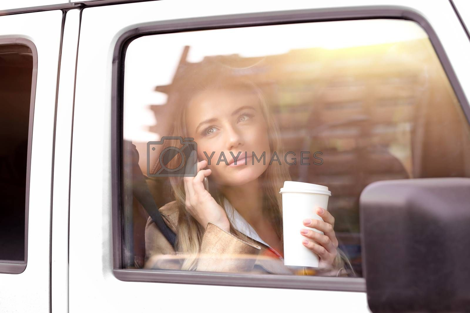 Portrait of a beautiful serious business woman having coffee in the car, going to work and talking on the phone, wireless communication for young successful people