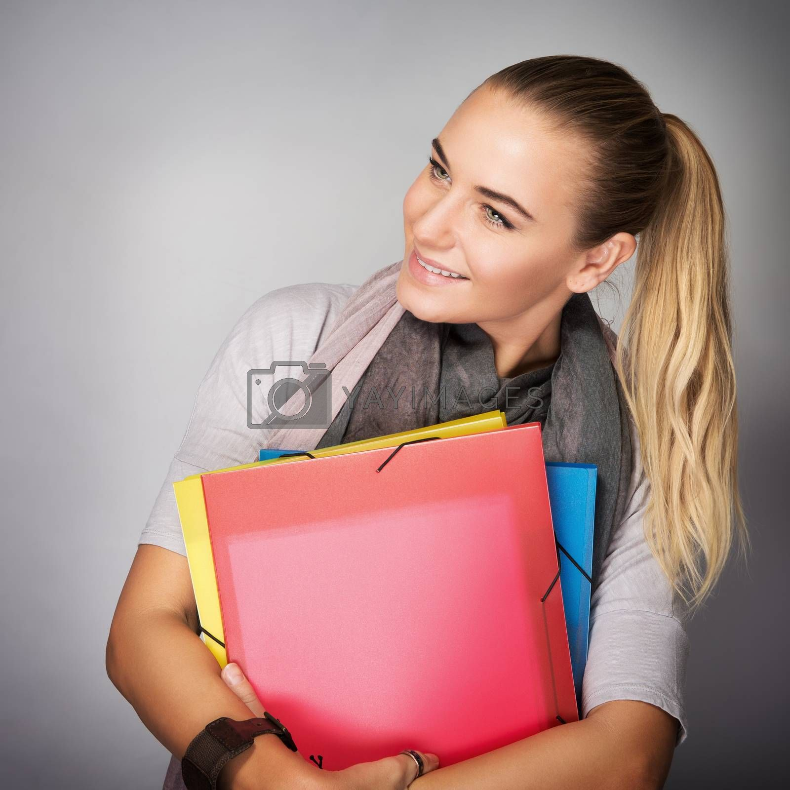 Portrait of nice student girl standing in the studio over gray background, with wonder looking in side, in anticipation of learning in higher education