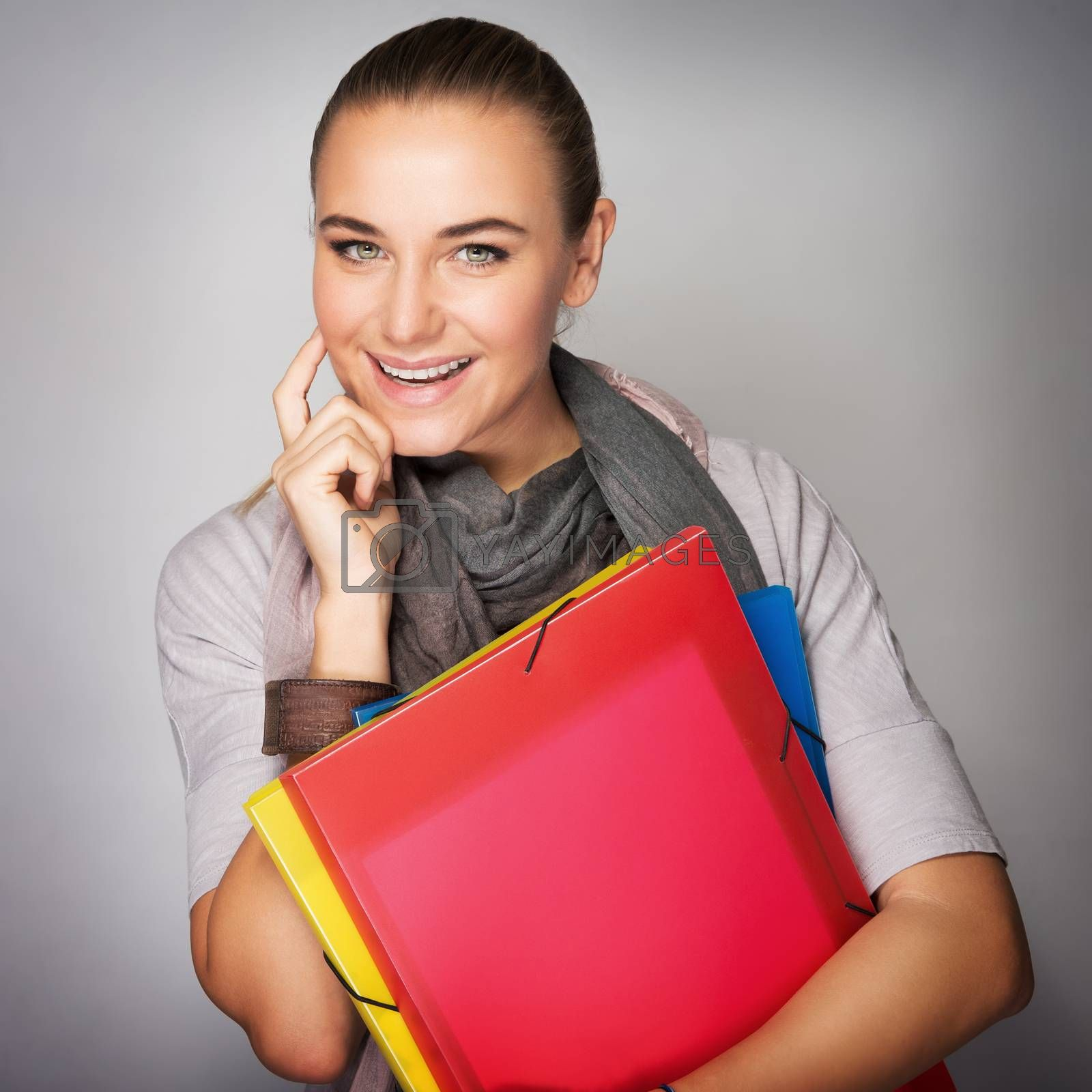 Portrait of nice student girl standing in the studio over gray background, holding in hands colorful folders for paper, in anticipation of learning in higher education