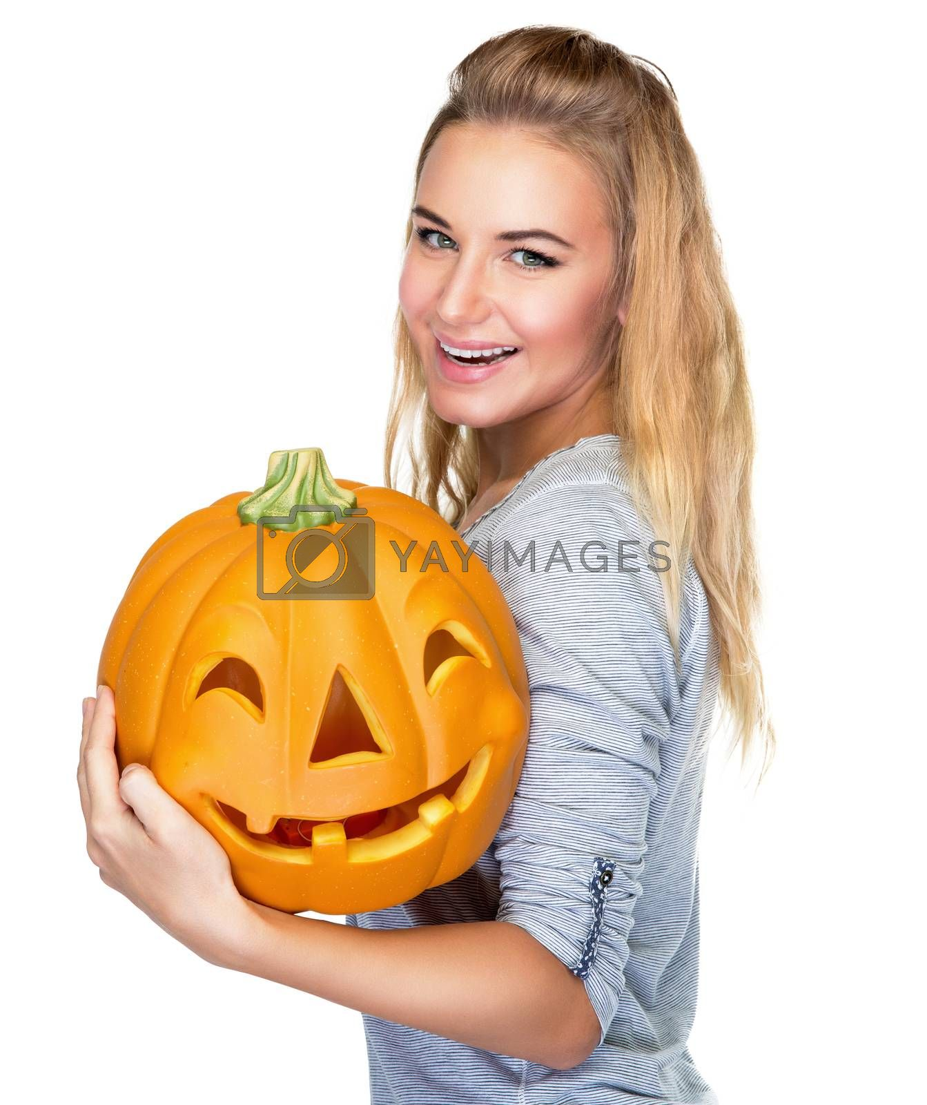 Portrait of beautiful blond female with holding in hands pumpkin with carved face isolated on white background, happy Halloween holiday