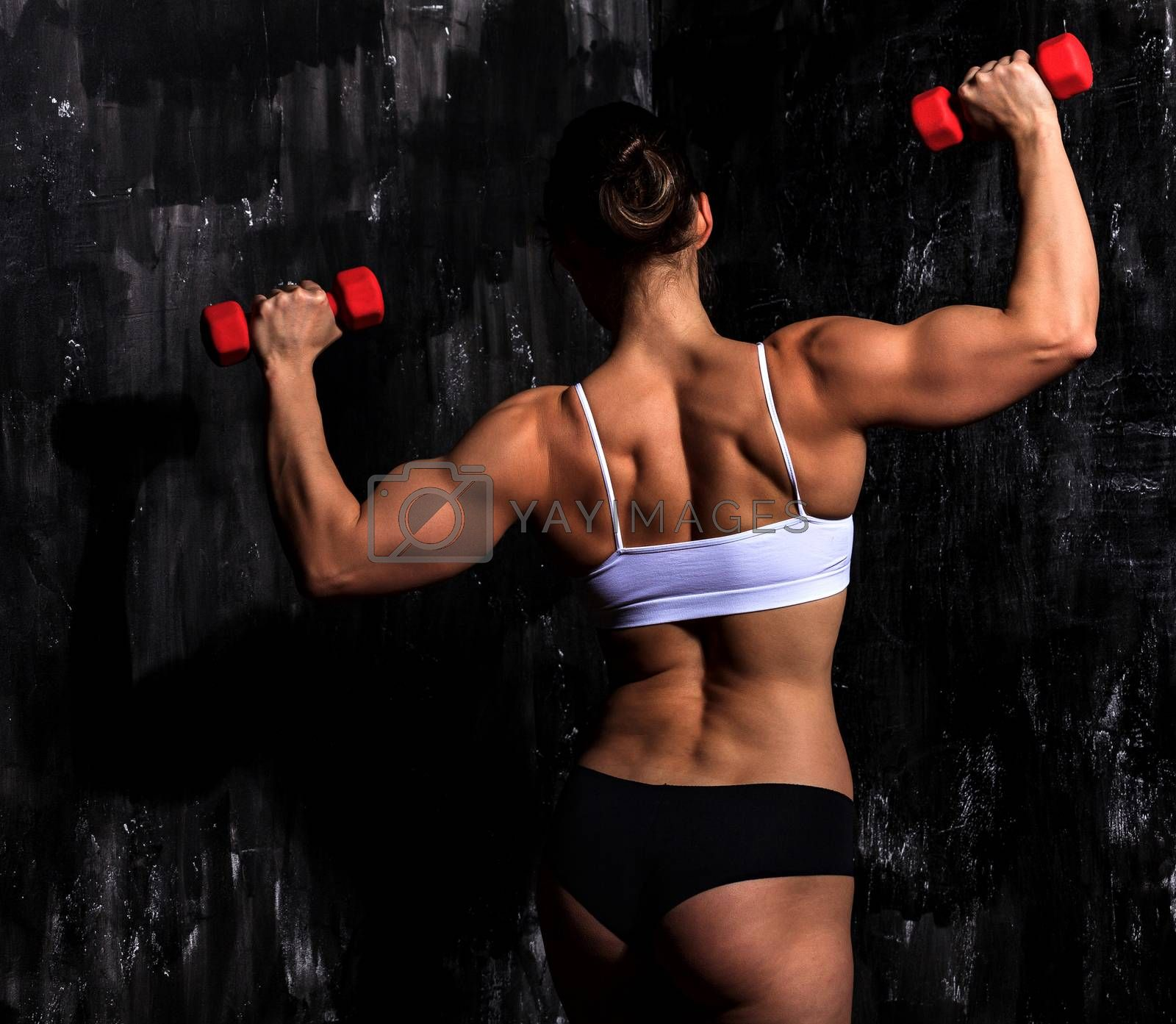 Fitness woman with red dumbbells on a dark background by Nobilior