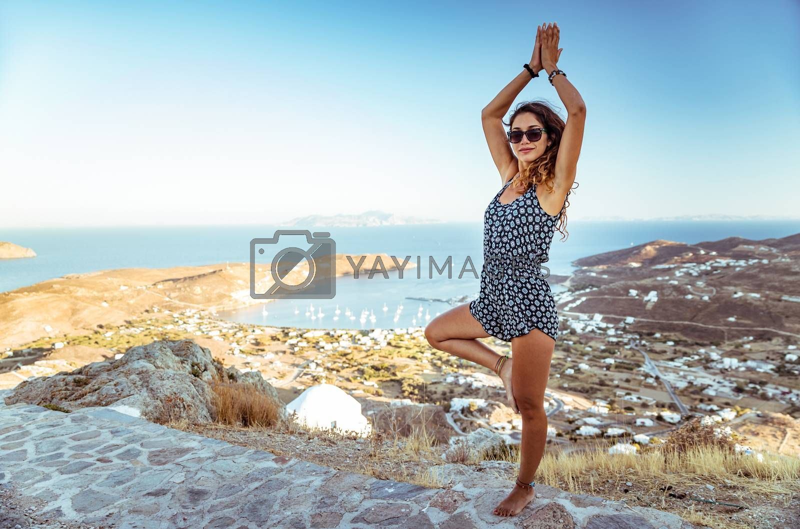 Woman meditating outdoors, beautiful female standing in yoga asana on the mountain near seaside, peaceful vacation on the beach, zen and soul balance concept