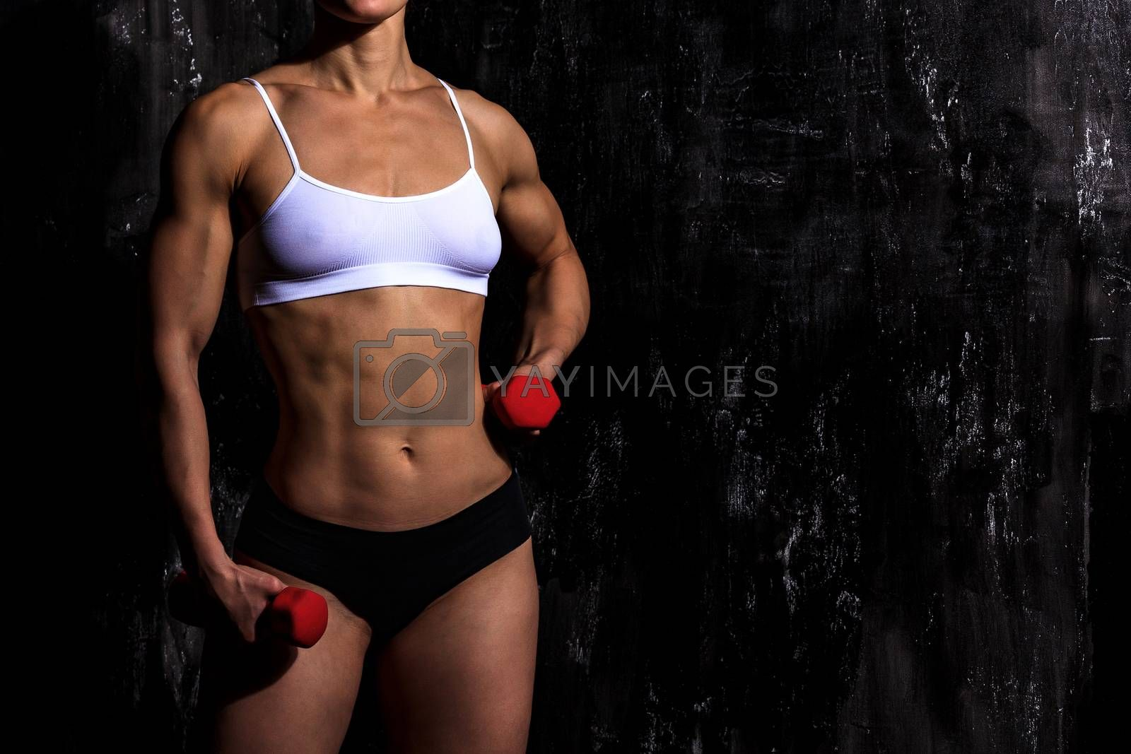 Fitness woman with red dumbbells on a dark background