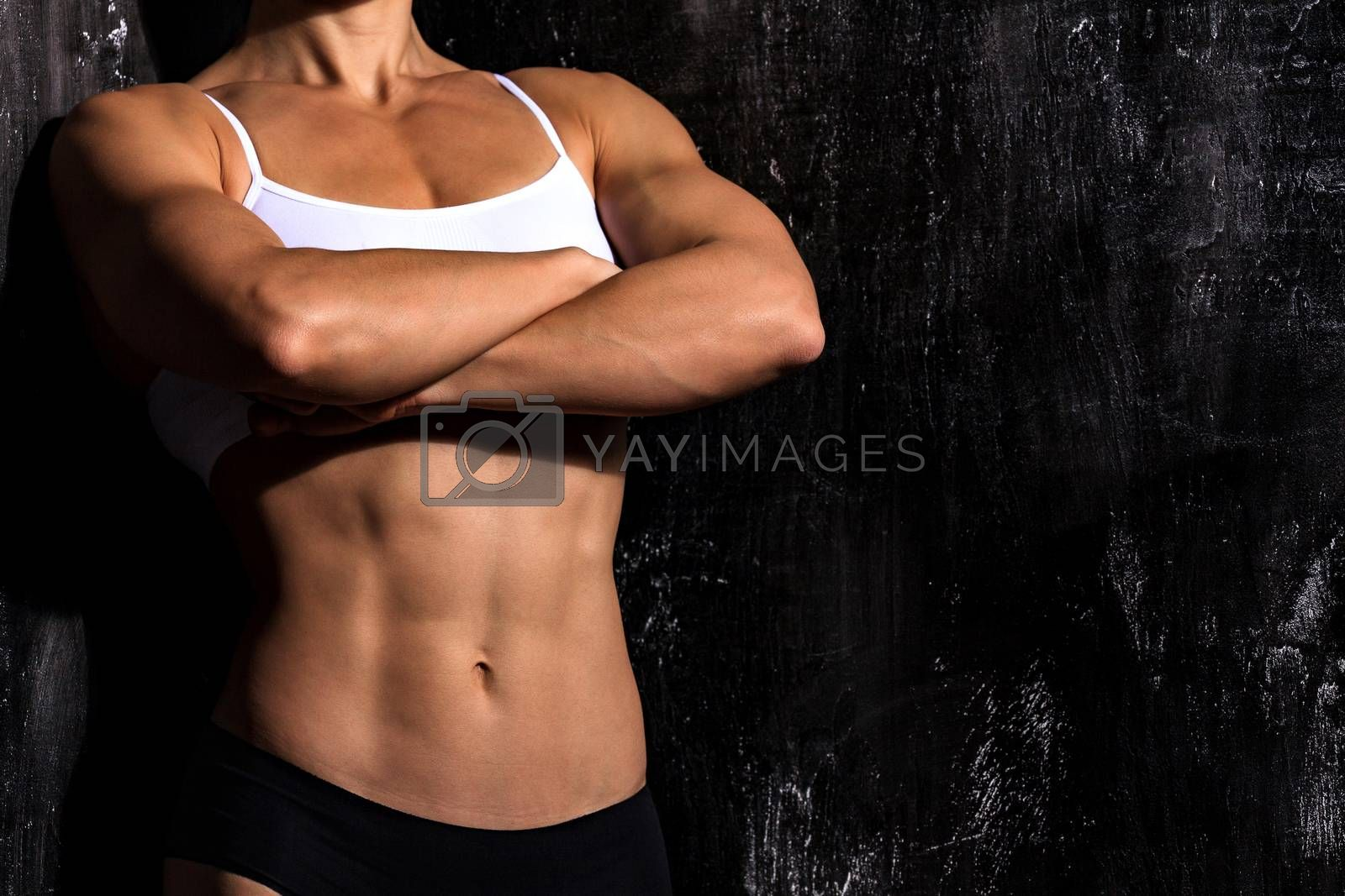 Muscular female torso wearing fitness clothing is posing against by Nobilior