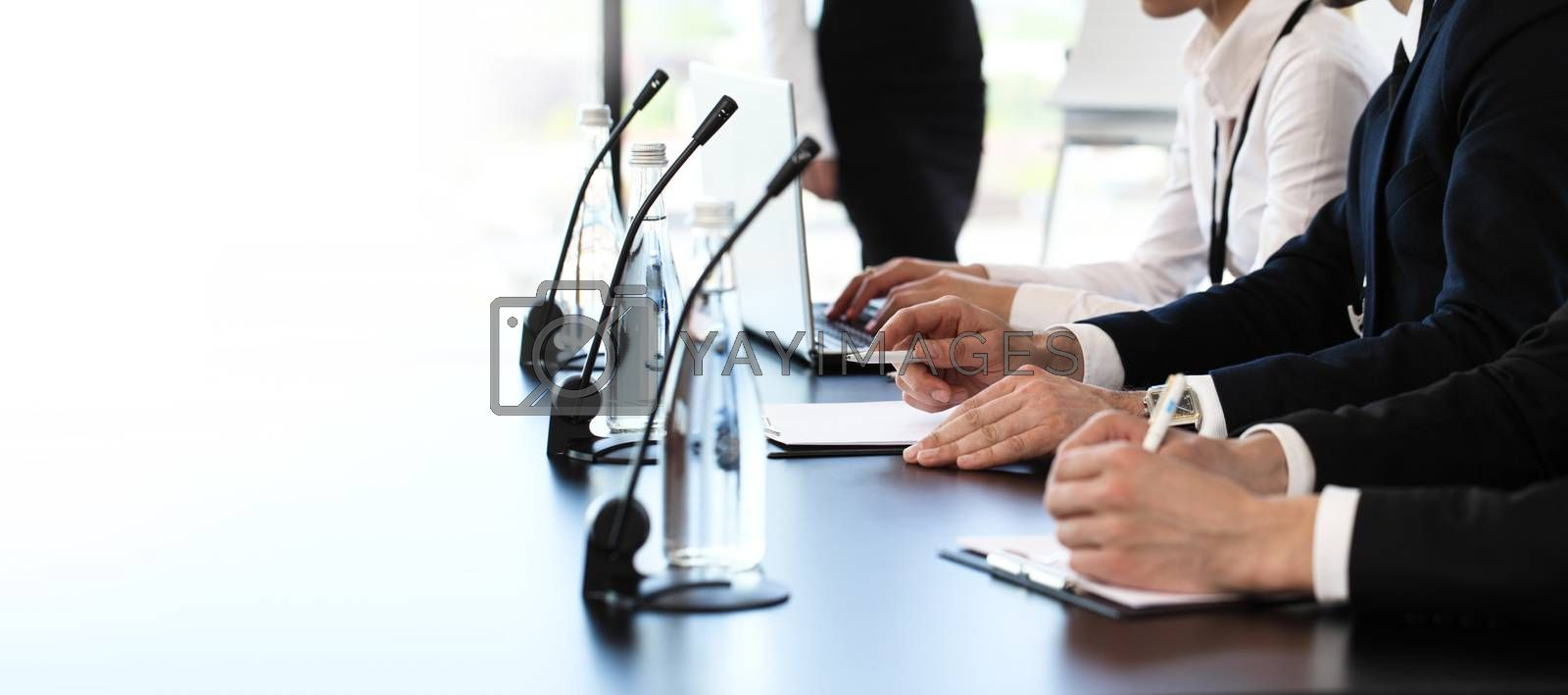Group of speakers at business meeting at the table with microphones