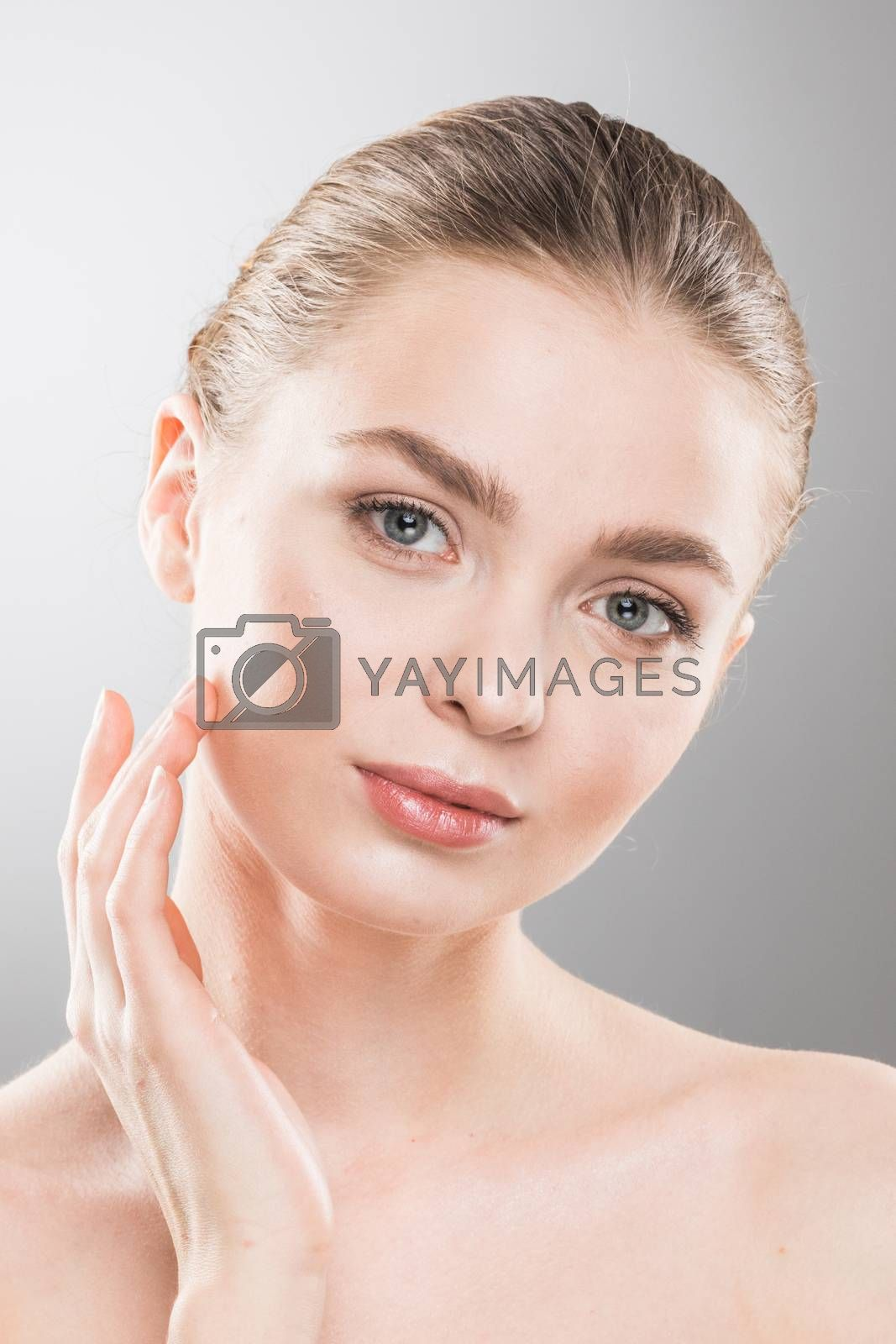 Beautiful young woman with clean fresh skin touch own face. Facial treatment. Cosmetology, beauty and spa