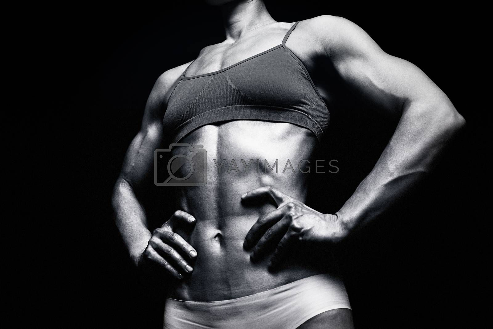 Fitness woman posing against a black background by Nobilior
