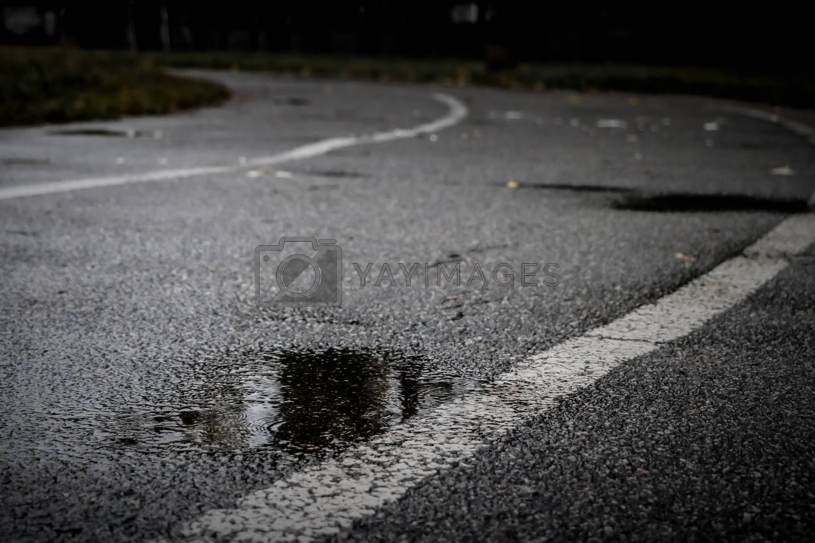 Asphalt track at an old school stadium during a rain with a puddle in the foreground. Dark autumn day