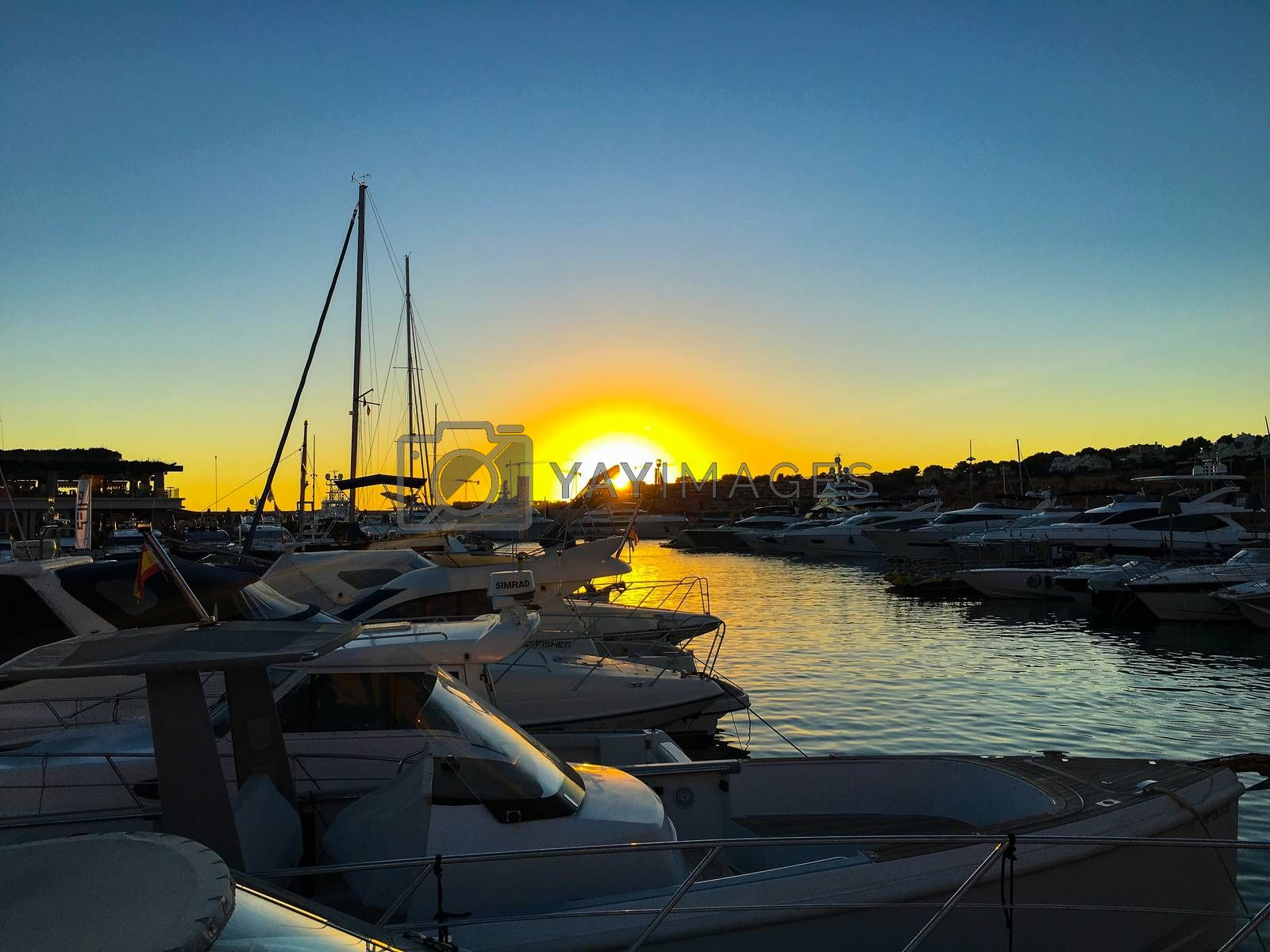 wonderful sunset at the pier with sailboats in front