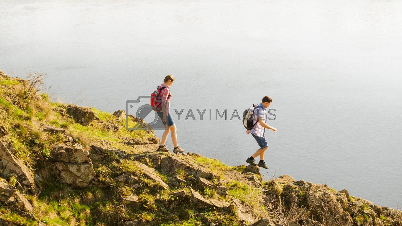 Couple of Young Happy Travelers Hiking with Backpacks on the Beautiful Rocky Trail at Warm Sunny Evening. Family Travel and Adventure Concept.